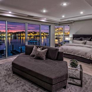 Großes Modernes Hauptschlafzimmer mit hellem Holzboden, Kaminumrandung aus Beton, beigem Boden und grauer Wandfarbe in Orange County