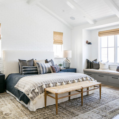 Example of a beach style master dark wood floor and brown floor bedroom design in Orange County with white walls