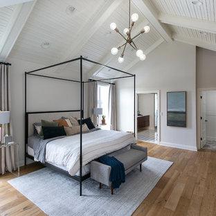 Стильный дизайн: большая хозяйская спальня в стиле современная классика с белыми стенами, стандартным камином, фасадом камина из дерева, коричневым полом и паркетным полом среднего тона - последний тренд