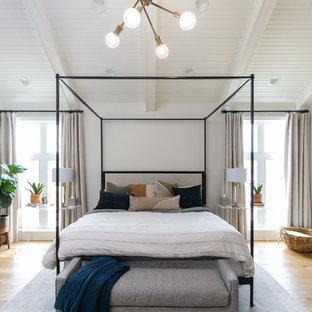 Imagen de dormitorio principal, tradicional renovado, grande, con paredes blancas, suelo de madera clara, chimenea tradicional, marco de chimenea de madera y suelo beige