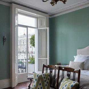 Idée de décoration pour une grand chambre parentale victorienne avec un mur vert, un sol marron et un sol en bois brun.
