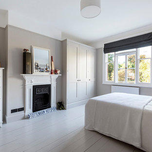 Photo of a classic bedroom in Other with grey walls, painted wood flooring, a standard fireplace, a metal fireplace surround and grey floors.
