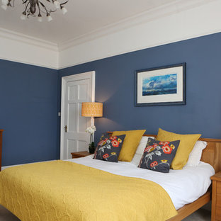 Large traditional master bedroom in Dorset with blue walls, carpet and no fireplace.