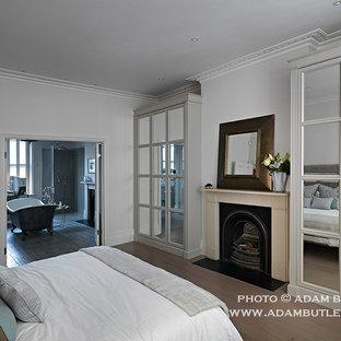Ispirazione per una camera matrimoniale minimal di medie dimensioni con pareti grigie, pavimento in legno massello medio, camino classico e cornice del camino in legno