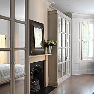 ロンドンの中くらいのコンテンポラリースタイルのおしゃれな主寝室 (グレーの壁、無垢フローリング、標準型暖炉、木材の暖炉まわり) のレイアウト