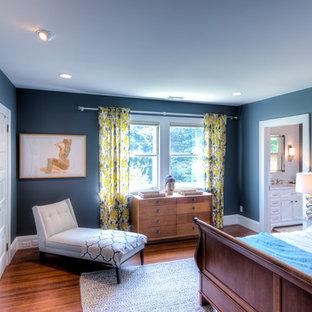 Foto de dormitorio principal, de tamaño medio, con paredes azules, suelo de madera clara, chimenea tradicional y marco de chimenea de ladrillo