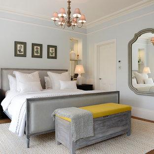 Immagine di una camera matrimoniale vittoriana con pareti blu e pavimento in legno massello medio