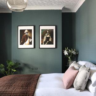 Modelo de dormitorio principal, de tamaño medio, sin chimenea, con paredes verdes, suelo de madera en tonos medios y suelo marrón