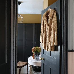 Ejemplo de habitación de invitados de tamaño medio, sin chimenea, con paredes amarillas, suelo de madera en tonos medios y suelo marrón