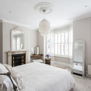 Inspiration for a large traditional master bedroom in London with grey walls, carpet, a standard fireplace and a stone fireplace surround.