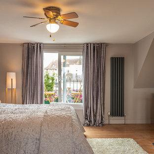 Ejemplo de dormitorio principal, contemporáneo, grande, con paredes marrones y suelo de contrachapado