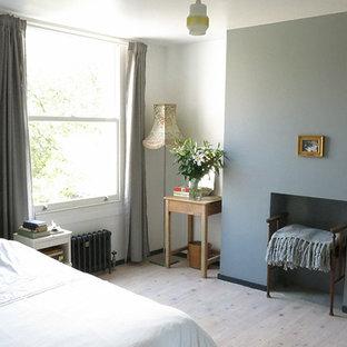 Свежая идея для дизайна: гостевая спальня среднего размера в скандинавском стиле с разноцветными стенами, светлым паркетным полом, стандартным камином и фасадом камина из штукатурки - отличное фото интерьера