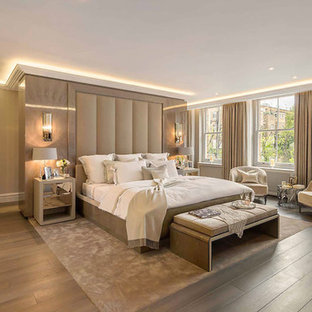 Expansive transitional master bedroom in London with beige walls, medium hardwood floors and brown floor.