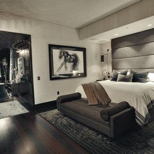 Immagine di una camera matrimoniale design di medie dimensioni con pareti beige, parquet scuro, nessun camino e pavimento marrone