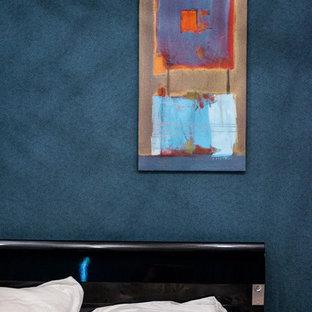 Modelo de dormitorio principal, bohemio, grande, con paredes azules, moqueta y suelo violeta
