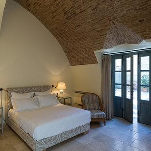 Imagen de habitación de invitados pequeña, sin chimenea, con paredes multicolor, suelo de piedra caliza y marco de chimenea de piedra