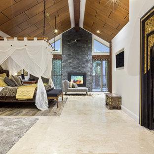 Foto de dormitorio principal, exótico, extra grande, con chimenea de doble cara, marco de chimenea de piedra y suelo multicolor