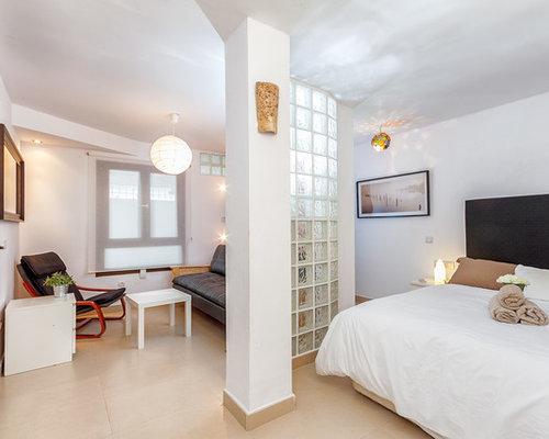 Camera da letto stile loft mediterranea con pavimento con