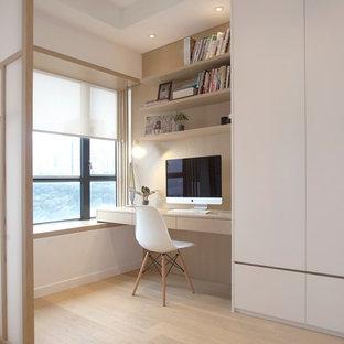 Imagen de dormitorio principal, moderno, de tamaño medio, con paredes blancas y suelo de madera clara