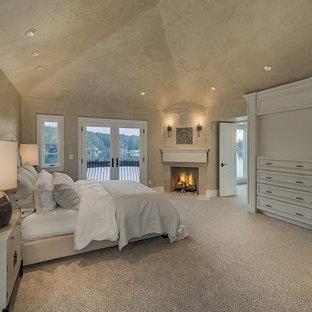 Cette photo montre une très grande chambre méditerranéenne avec un mur beige, une cheminée d'angle, un manteau de cheminée en pierre et un sol beige.