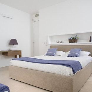 Immagine di una camera matrimoniale mediterranea con pareti bianche e pavimento in gres porcellanato