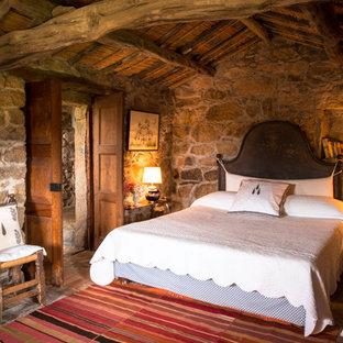 Стильный дизайн: хозяйская спальня среднего размера в стиле рустика с кирпичным полом и коричневыми стенами - последний тренд