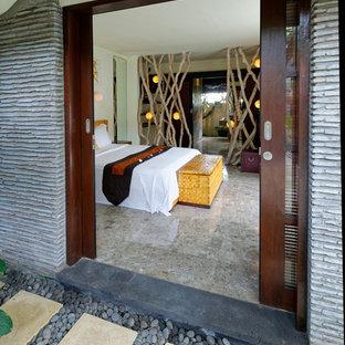 Imagen de dormitorio principal, tropical, grande, con paredes blancas, suelo de piedra caliza y suelo gris