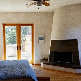他の地域の大きい地中海スタイルのおしゃれな主寝室 (ベージュの壁、無垢フローリング、標準型暖炉、漆喰の暖炉まわり、茶色い床) のインテリア