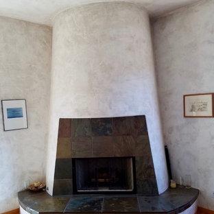 他の地域の大きい地中海スタイルのおしゃれな主寝室 (ベージュの壁、無垢フローリング、標準型暖炉、漆喰の暖炉まわり、茶色い床) のレイアウト