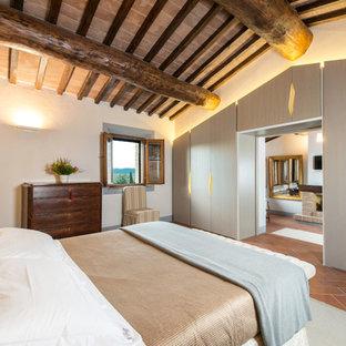 Diseño de dormitorio principal, actual, grande, con paredes blancas, suelo de ladrillo, chimenea tradicional y marco de chimenea de piedra