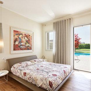 Immagine di una camera matrimoniale design con pareti beige, pavimento in legno massello medio e pavimento marrone