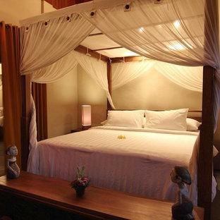 Ejemplo de dormitorio principal, tropical, de tamaño medio, con suelo de piedra caliza