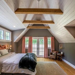 Ejemplo de dormitorio principal, de estilo de casa de campo, con paredes grises, suelo de madera en tonos medios y suelo marrón