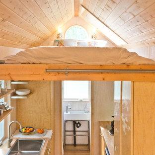 Modelo de dormitorio tipo loft, actual, pequeño, sin chimenea, con paredes blancas y suelo de madera en tonos medios