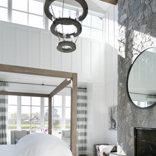 Landhausstil Schlafzimmer mit weißer Wandfarbe, braunem Holzboden, Kamin, Kaminumrandung aus Stein, braunem Boden, freigelegten Dachbalken, Holzdielendecke, gewölbter Decke und Wandpaneelen in Orange County