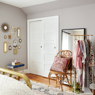 This is an example of a mid-sized eclectic master bedroom in Philadelphia with purple walls, medium hardwood floors, no fireplace and brown floor.