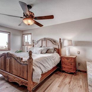 Imagen de dormitorio principal, tradicional, de tamaño medio, con paredes beige, suelo de madera clara, chimenea de doble cara y marco de chimenea de ladrillo