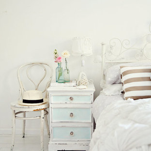 Cottage chic light wood floor and white floor bedroom photo in Sydney with white walls