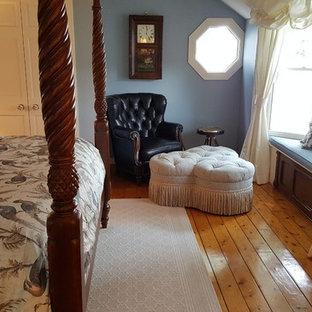 Imagen de dormitorio principal, tradicional, grande, sin chimenea, con paredes azules, suelo de madera en tonos medios y suelo marrón