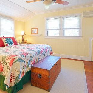 ハワイの広いトロピカルスタイルのおしゃれな主寝室 (黄色い壁、無垢フローリング)