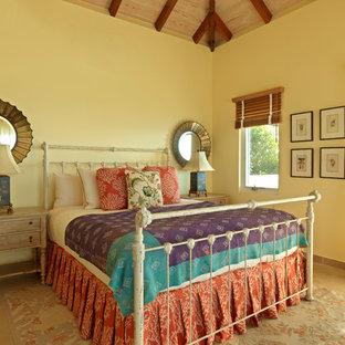 Ejemplo de dormitorio tipo loft, costero, pequeño, con paredes amarillas y suelo de piedra caliza