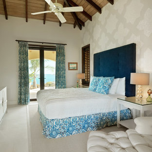 Design ideas for a mid-sized beach style loft-style bedroom in Other with beige walls and limestone floors.