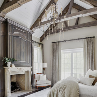 Design ideas for a bedroom in Other with beige walls, dark hardwood floors, a standard fireplace, brown floor, exposed beam and vaulted.