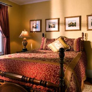 Modelo de habitación de invitados tradicional, pequeña, con paredes amarillas y suelo de madera en tonos medios