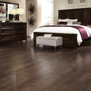 Large trendy master dark wood floor and brown floor bedroom photo in Other with beige walls
