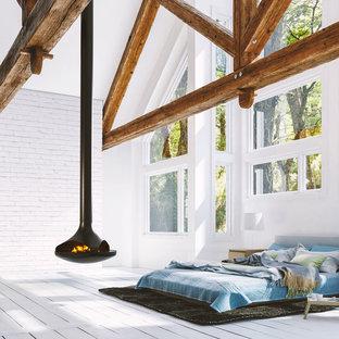 Foto di una camera da letto chic con camino sospeso