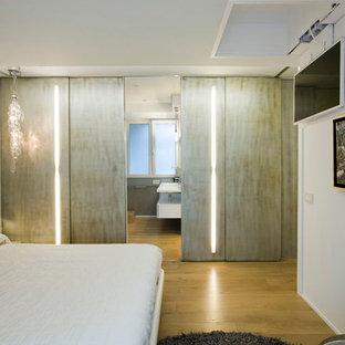 Modelo de dormitorio principal, contemporáneo, de tamaño medio, sin chimenea, con paredes blancas y suelo de madera clara