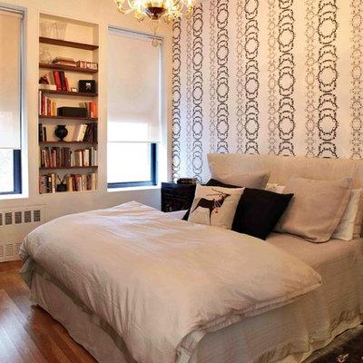 Example of a trendy medium tone wood floor bedroom design in New York with beige walls