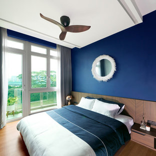 This is an example of a contemporary bedroom in Singapore with blue walls, light hardwood flooring and brown floors.