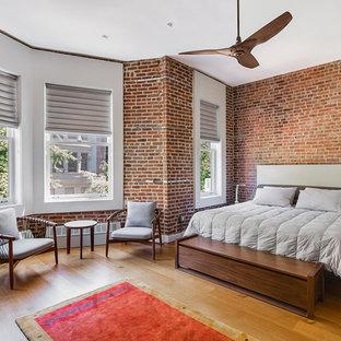 Diseño de dormitorio principal, urbano, con paredes rojas y suelo de madera en tonos medios